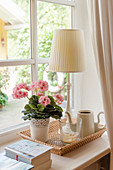 Table lamp, potted geranium and teapot on cork tray on windowsill