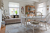 Spoke-back chairs around table in rustic, white living space