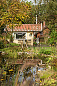 Yellow summerhouse and pond in late summer garden