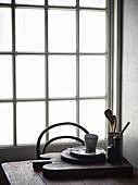 Schneidebrett mit Küchenutensilien und Geschirr auf Holztisch vor Fenster