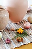 Vasen, Ostereier, Strohblumen und Farnblatt als Tischdeko zu Ostern