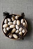Eier aus Holz und Keramik und braune Federn in einer Holzschale