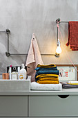 Horizontal and vertical metal rods mounted on wall as towel rail and lamp holder