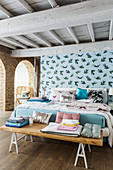 Double bed and bedroom bench in front of pale blue partition wall with pattern of birds