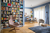 Blue interior with floor-to-ceiling bookcase and dining and seating areas