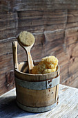 Bath sponge and brush in wooden bucket