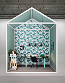 Creative design for study area with desk against wall covered in leaf-patterned wallpaper