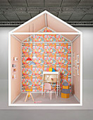 Creative design for study area with desk against wall covered in geometric wallpaper