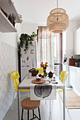 Beige accents and dining table with lemon-yellow chairs in bright kitchen
