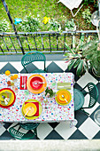 Terrace table set with floral tablecloth and brightly coloured place settings