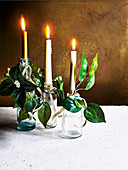 Christmas centrepieces: bottles with candles, foliage and gold ribbons