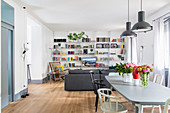 Dining table in front sofa, rocking chair and bookcase in seating area in open-plan interior