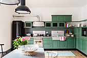 Green, country-house-style kitchen with industrial lamps over dining table