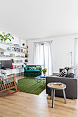 Grey sofa, rocking chair and green vintage-style armchair in seating area around TV