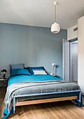 Bett mit blau-grauer Bettwäsche in Schlafzimmer mit blau gestrichenen Wänden