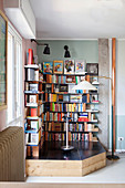 Bookcase made from bricks and metal shelves on platform in corner of room