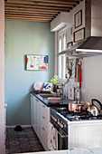 Mint-green wall, white kitchen counter and patterned floor tiles in kitchen area