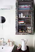 Ornaments and utensils in glass-fronted, shabby-chic, wall-mounted bathroom cabinet