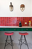 Bar stools under counter in retro red-and-green kitchen