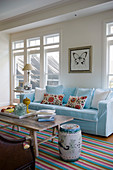 Brightly striped rug and pale blue sofa in exotic living room