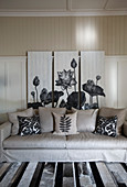 Floral triptych behind sofa in living room in shades of grey