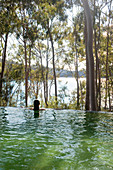 Infinity pool with view of woodland and lake