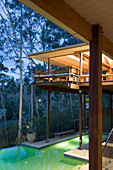 Modern, architect-designed wooden house on stilts with pool illuminated at twilight