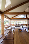 Dining table in spacious living area of modern, open-plan wooden house