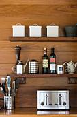 Küchenutensilien auf Arbeitsplatte und Regalbrettern vor Holzwand