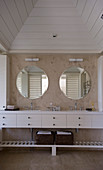 Twin sinks with white base units below round mirrors in beach house