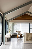 Simple living room below gable roof with exposed steel beams