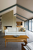 Fireplace in open-plan interior below gable roof with exposed steel beams