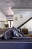 Blue sofa in interior with staircase and silver stucco ceiling