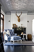Blue-and-white armchair and footstool with toile de jouy upholstery in front of fireplace below hunting trophy