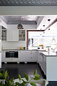 L-shaped kitchen counter with white base units in open-plan kitchen with dark wooden floor