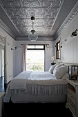 Double bed in bedroom with silver stucco ceiling