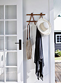Cloakroom with sun hat, cloth and bag on white wall next to rung door