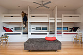Bunk beds in bedroom with girl climbing down ladder