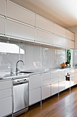 White kitchen counter with stainless steel trim and splashback
