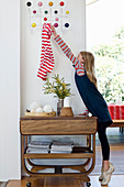 Girl hanging clothing on Eames Hang-It-All coat rack above serving trolley