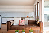 Cognac leather couch in front of white kitchen counter in open-plan interior