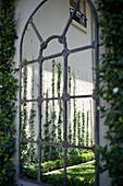 Arched iron window frame in garden wall