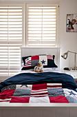 Bettwäsche mit 'Stars and Strips' Motiv auf Bett im Jugendzimmer