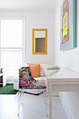 Simple white desk with colourful chair, armchair and mirror