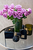 Vase of purple roses, perfume and jewellery box on side table