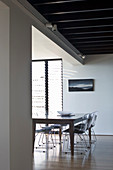 Dining table and metal chairs in open-plan interior