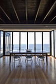 Dining table and metal chairs in front of glass wall with sea view
