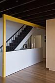 Blick auf Treppe im Wohnraum mit gelb lackiertem Balken