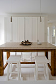 Wooden table with marble top and white stools in front of white cupboard