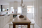 Wooden table with marble top and stools in white kitchen